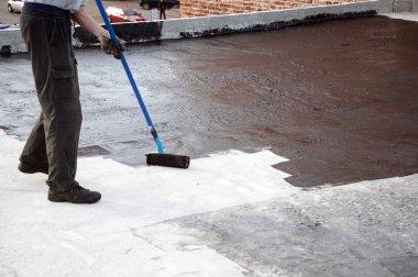 Roofer worker painting  bitumen praimer at concrete surface by t