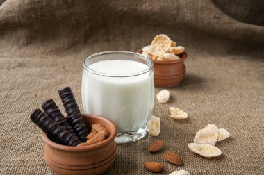 A glass of milk with almond nuts, corn flakes, chocolates,  on burlap background