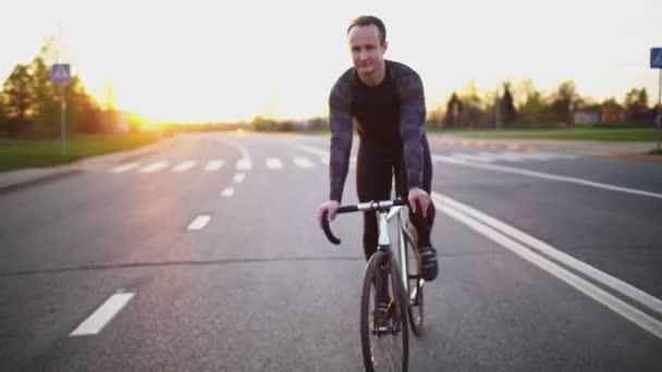 Muž na koni kotvené zařízení kolo na silnici při západu slunce v pomalém pohybu