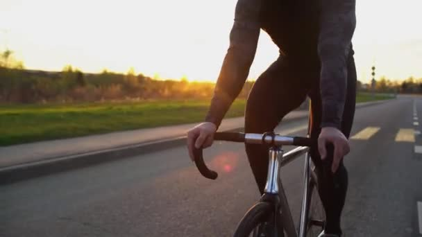 Muž na koni kotvené zařízení kolo na silnici při západu slunce