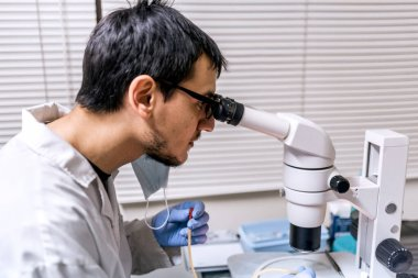 Stock photo of male scientist wearing face mask using a microscopy in his lab.