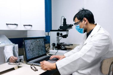 Stock photo of male scientist wearing face mask using the computer and a microscopy in his lab.