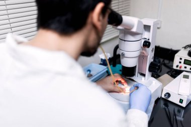 Stock photo of male scientist using a microscopy in his lab.