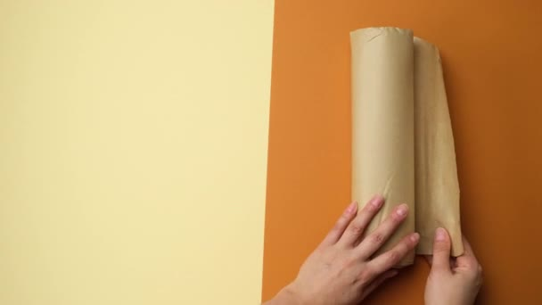 female hand cuts a piece of paper with scissors from a roll of brown parchment paper, view from the top