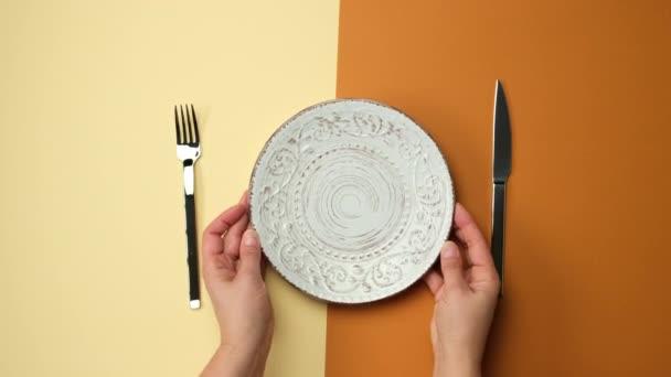bílý kulatý talíř, nůž s vidličkou na hnědém pozadí, samičí ruka vloží suchý žlutý list do talíře, horní pohled