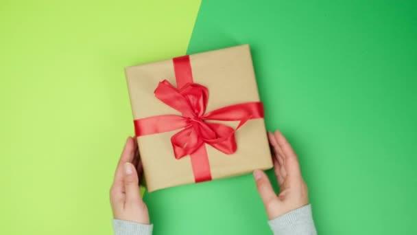 zwei weibliche Hände im Pullover halten eine quadratische braune Schachtel mit roter Schleife auf grünem Hintergrund, Draufsicht, festlicher Hintergrund