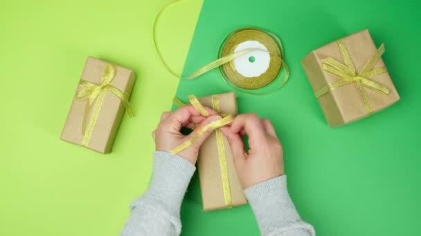 Frau verpackt Geschenke in braunes Papier und goldenes Band, grüner Hintergrund, Ansicht von oben