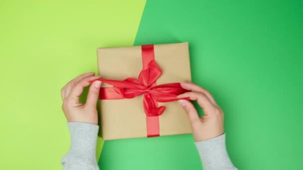 női kéz oldja piros selyem szalag ajándék doboz, zöld háttér, felső nézet