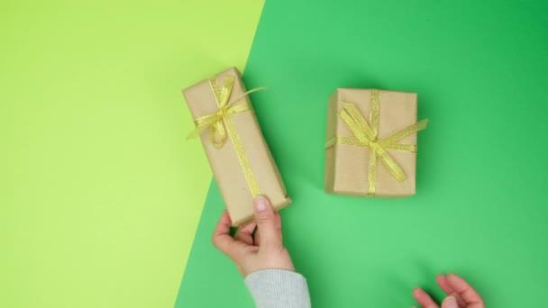 dvě ženské ruce položil na zelený povrch krabici s dárky svázané zlatou stuhou, horní pohled