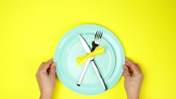 két női kéz tesz fém kés és villa kötött sárga szalaggal üres lemezek, felső nézet, sárga háttér, asztali beállítás