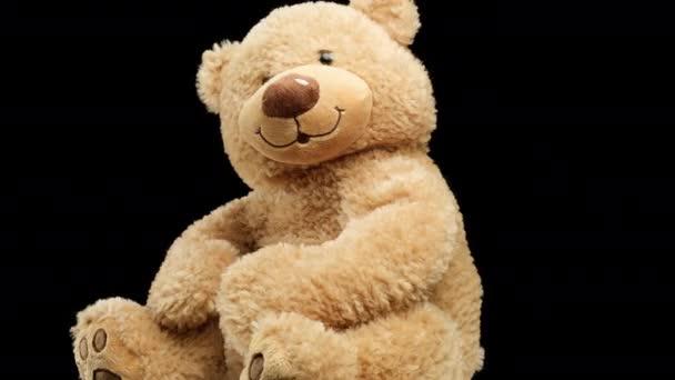 nagy barna játékmackó egy mosoly forog a fekete háttér, gyermekjáték