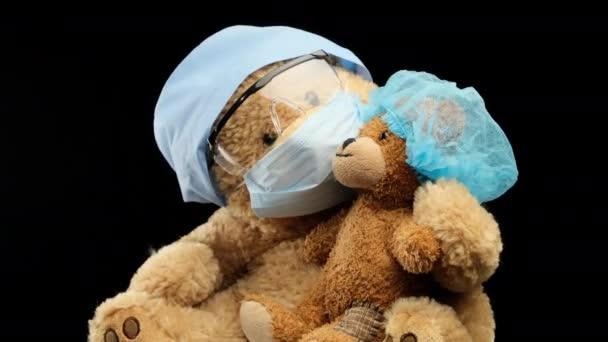 Brauner Teddybär sitzt in schützender Plastikbrille, medizinischer Einmalmaske und blauer Mütze, Konzept der Kinderheilkunde, schwarzer Hintergrund