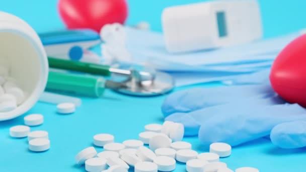 verstreute runde weiße Pillen auf blauem Hintergrund, Kameras vorwärts, Zeitlupe