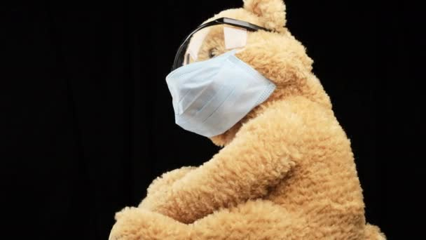 brown teddy bear sits in protective plastic glasses, a medical disposable mask, concept of pediatrics, black background