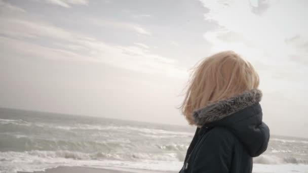 Mladá blondýnka, vyhřívají na slunci na pláži a usmívá se ve větru