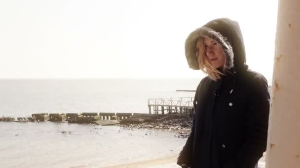 Young blond girl in warm clothes basking in the sun on the beach and smiling