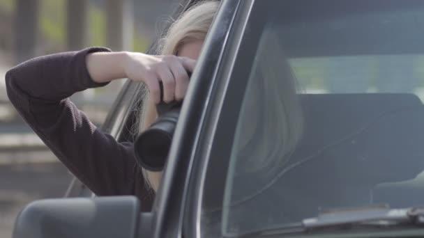 Blondes Mädchen beobachtet und fotografiert mit professioneller Kamera im Auto