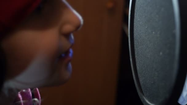 Photo Little girl in headphones singing into microphone in a recording studio