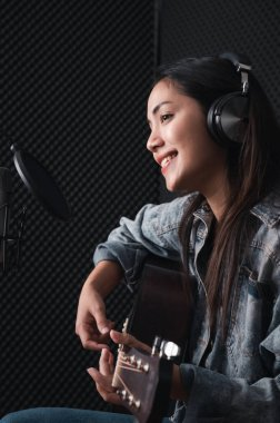Asian female singer with a passion for music and microphone. While playing her guitar in a professional studio. Music concept, sound recording concept.