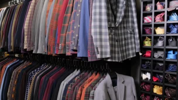 Pánské oblečení klasické různé obleky na ramínka v řadě v obchodě s oblečením v obchoďáku. Na regálech je spousta kostýmů. Obchodní a maloobchodní koncept.
