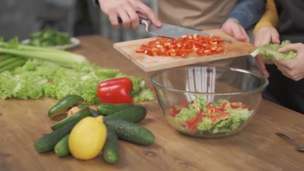 Nahaufnahme von Menschenhänden beim Schneiden von Gemüse auf einem Holzschneidebrett für Salat auf dem Tisch mit gesundem Essen in der Küche.