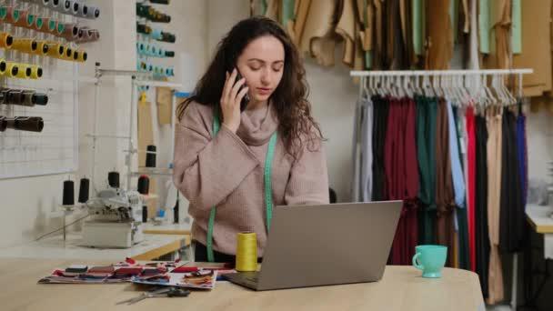 Úspěšný krejčí podnikatel mluví na mobilním telefonu a pomocí notebooku v ateliéru. Žena je zaneprázdněna objednáváním textilií od dodavatele textilu nebo objednávkou od zákazníka. Koncept spouštění designu oblečení. Malý podnik