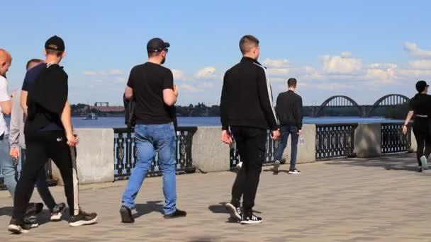 Mladí kluci, dívky, děti, dospělí chodí podél nábřeží u řeky, jezdí na kolech a skútrech. Léto, jarní rekreace, sporty v ukrajinském městě Dněpropro, Dněpropetrovsk, Ukrajina. 2021-05-15