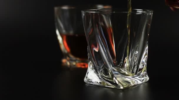 Whiskey, egy üveg fekete háttér ellenében öntik