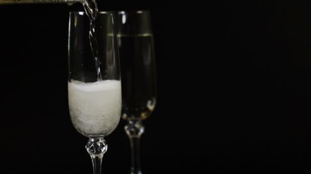Champagner wird in ein Glas auf schwarzem Hintergrund gegossen