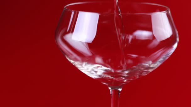 Champagne is poured into a glass on a red background