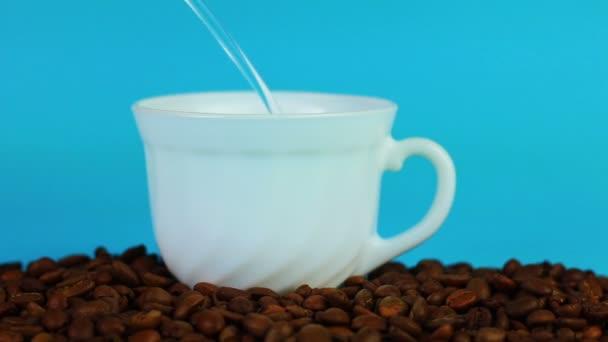 Šálek kávy a fazole na modrém pozadí