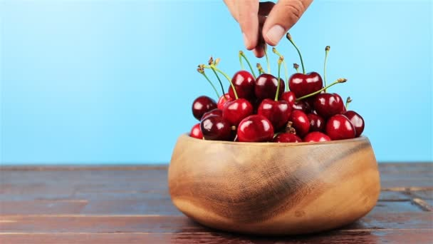 Mans hand take red cherries in wooden bowl on wooden table and blue background