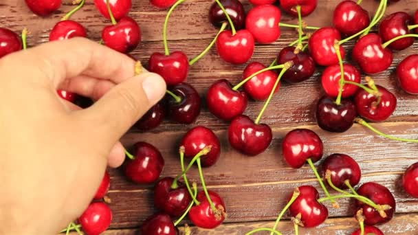 A mans hand take red ripe cherry on wooden table