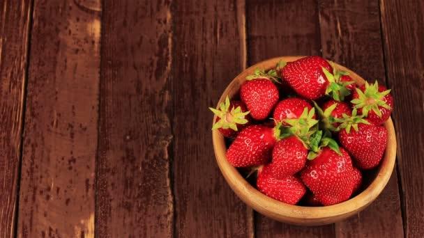 Mans ruku vzít červenou zralé jahody v dřevěné misce na dřevěný stůl