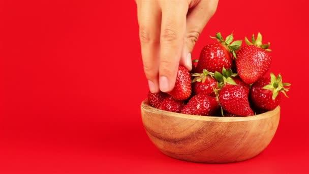 Mans ruku vzít červenou zralé jahody v dřevěné misce na červeném pozadí
