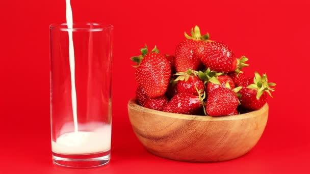 Mléko se nalije do sklenice a jahody v dřevěné misce na červeném pozadí