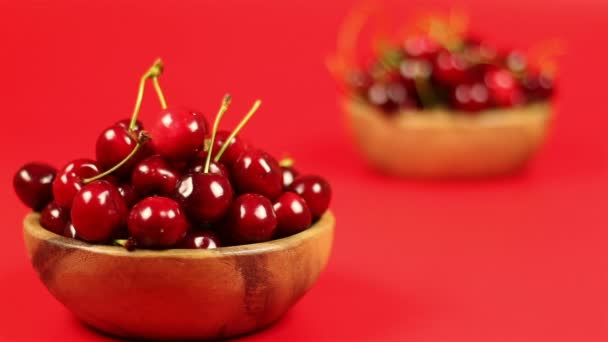 Two wooden bowls of cherries on red background