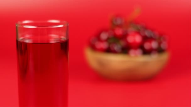 Red cherry juice in glass and red cherries in wooden bowl on red background