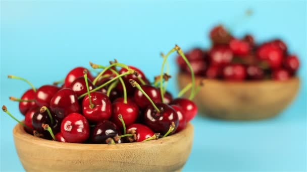 Two wooden bowls of cherries on blue background