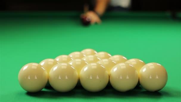 Červený míček zasáhne bílé koule v trojúhelníku na začátku kulečníkové hry