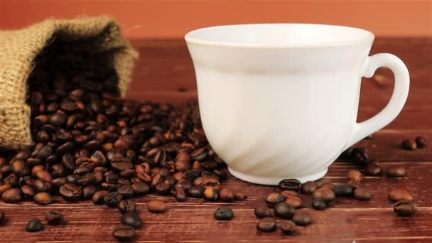 Káva se nalije do bílý šálek do straně pytel kávová zrna na hnědý dřevěný stůl
