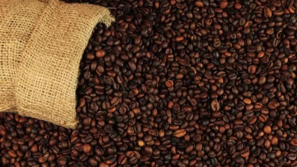Mladý muž dává šálek kávy na Pražení kávových zrn na hnědý dřevěný stůl