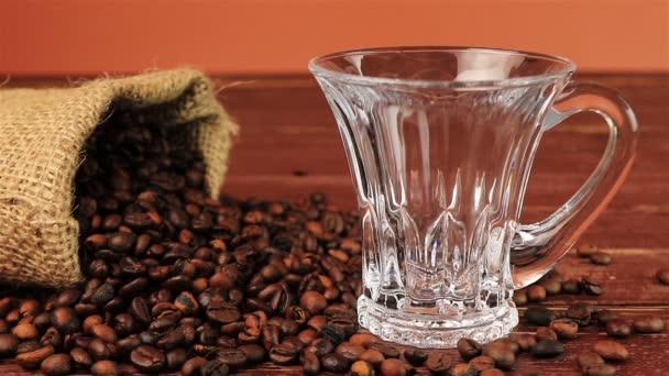 Kávé öntenek egy üveg csésze oldalán egy zsák szemes kávé barna fa tábla