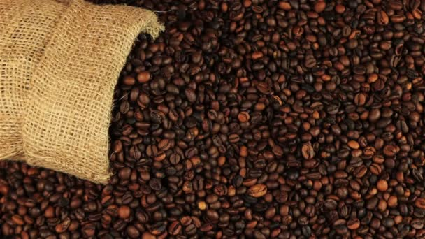 Young man puts a cup of coffee on roasting coffee beans on brown wooden table