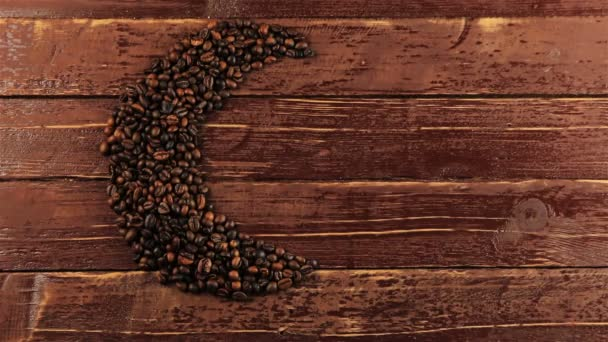 Young man puts a cup of coffee beside roasted black coffee beans arranged in a moon shape on dark background. Coffee beans in moon shape - Ramadan food concept