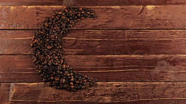 Fiatal férfi hozza egy csésze kávé mellett pörkölt fekete kávé bab rendezett Hold alakzat a sötét háttér előtt. Hold alakú - Ramadan élelmiszer koncepció szemes kávé