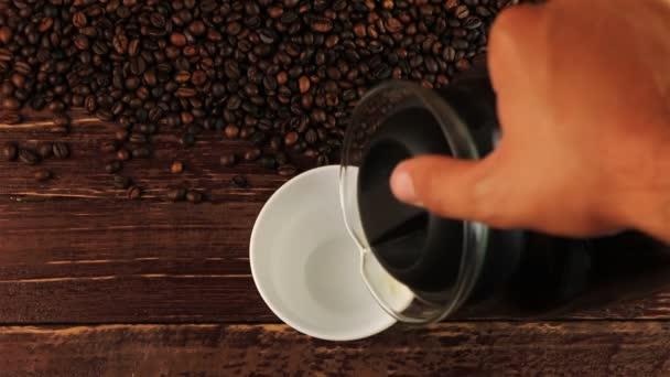 Nalijete kávu do bílé cup a kávová zrna na hnědý dřevěný stůl