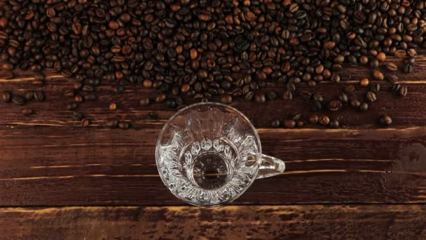 Pouring coffee into glass cup and coffee beans on brown wooden table