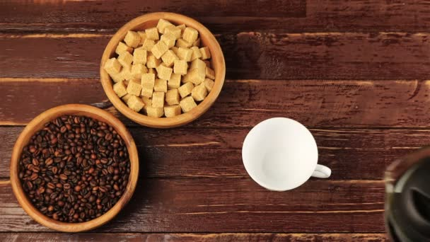 Coffee is poured into a white cup on the table on him located brown sugar cubes and roasted coffee beans in wooden plates on brown wooden table