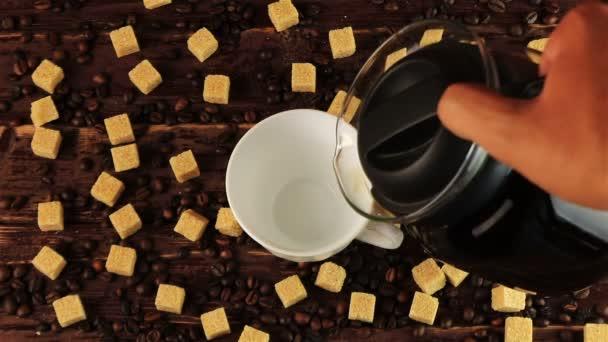 Kávé öntenek egy fehér csésze rá az asztalon található kávé bab és barna cukor kockák barna fa tábla